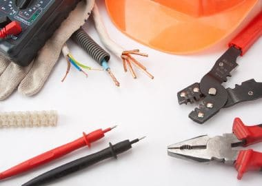 Electrician's tools. Hardhat, multimeter, pliers, cutter, cables, etc.